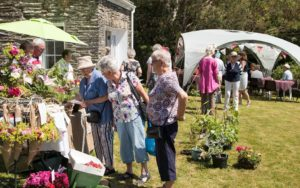 Open garden event hosted by St Brynach Parish Church, members of the public having a look at the flowers on a sunny day