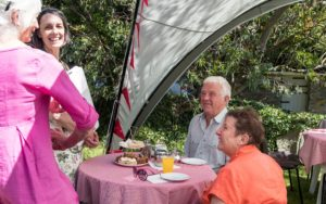 Open garden event hosted by a member of Nevern Church, an elderly couple sitting in the garden at a table talking with two women who are seeing that everyone is catered to